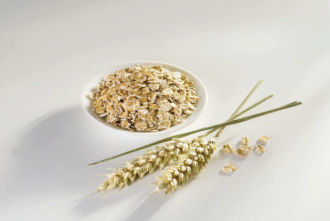 Wheat flakes in small dish, ears of wheat beside it