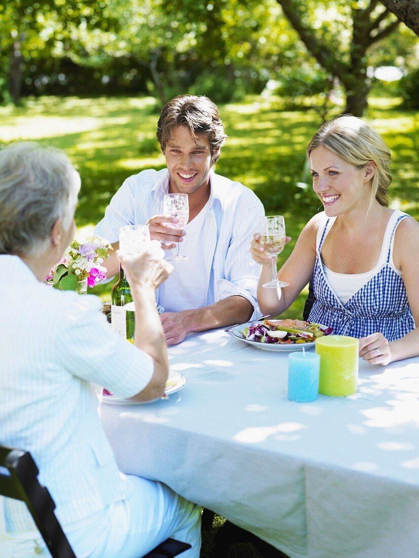 Family eating in the garden in summer