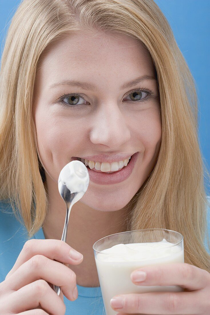 Young woman eating natural yoghurt