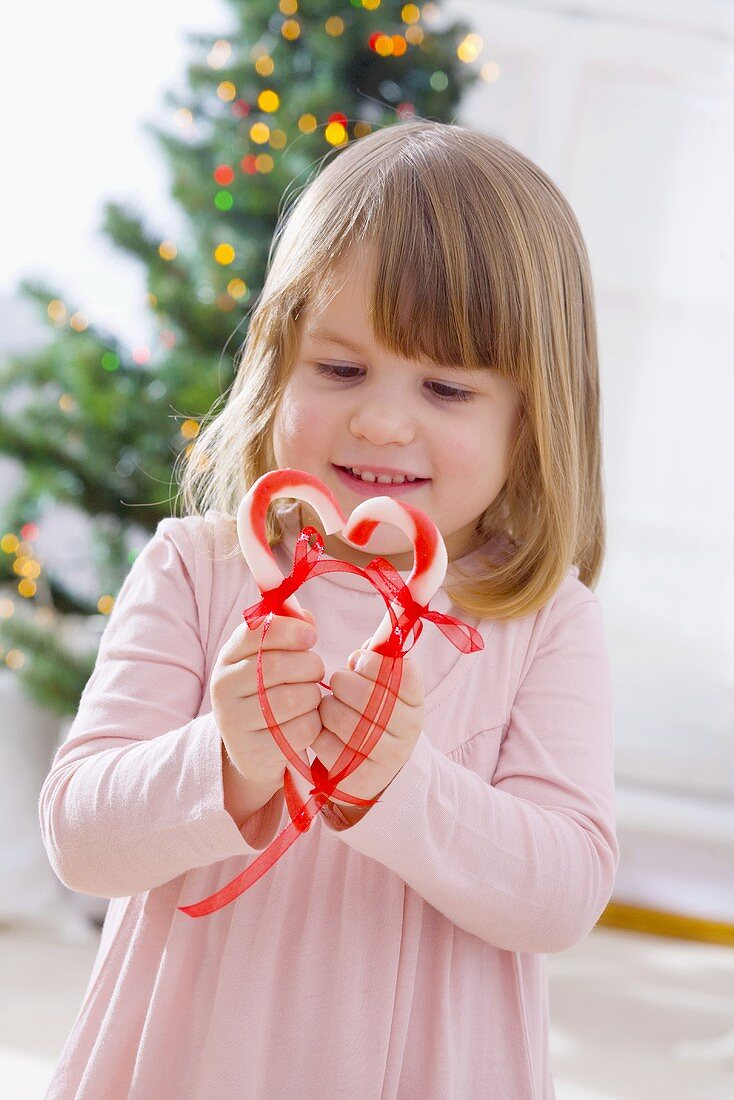 Little girl holding candy canes together to make a heart