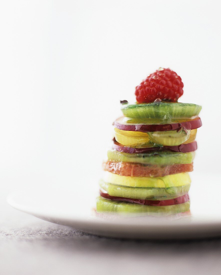 Tower of fresh fruit slices with mint and pepper sauce