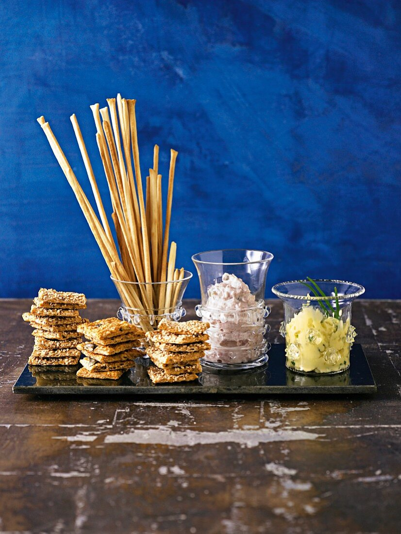 A cheese dip and a tuna dip with grissini and crispy crackers