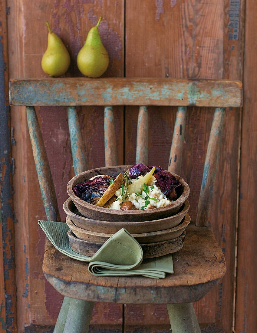 Pear and chestnut risotto on a plate on a rustic chair