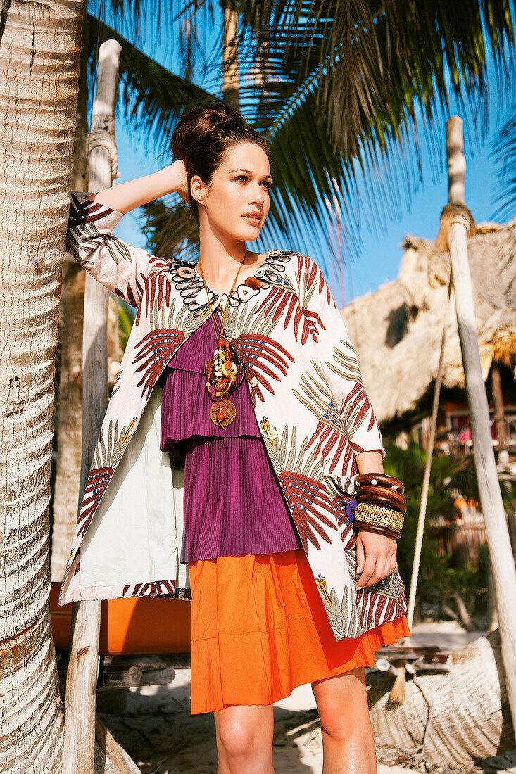 Frau stützt Kopf ab, lehnt an Palme, Safari-Look