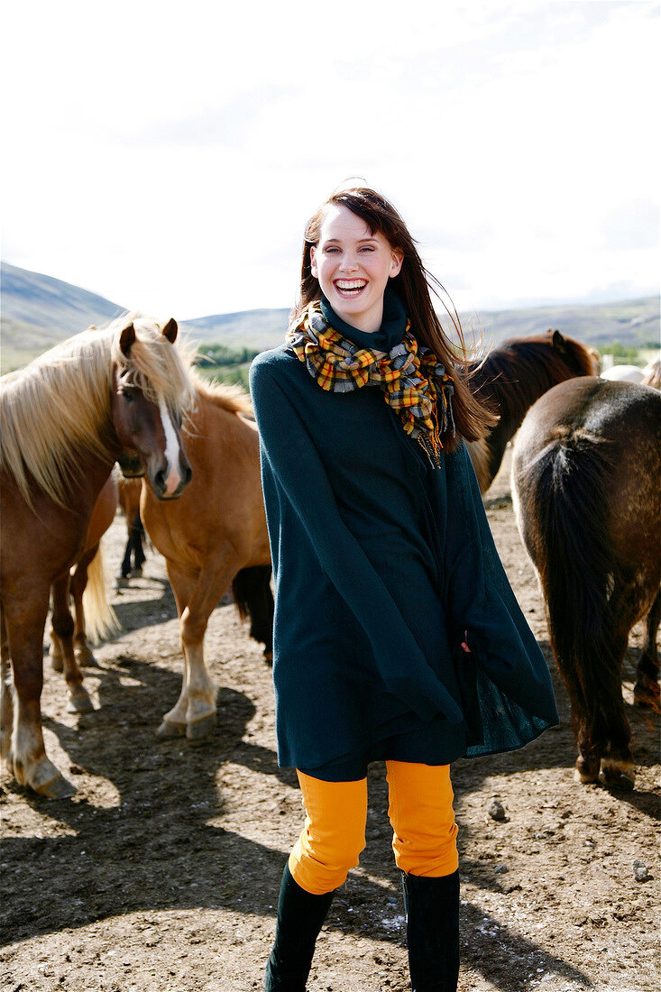 Happy woman wearing poncho and scarf standing in front of icelandic horses, laughing