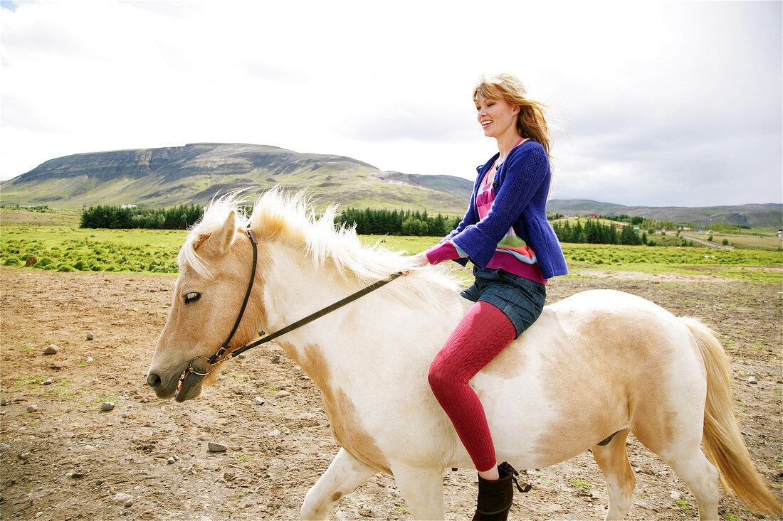 Happy blonde woman wearing blue sweater riding a piebald pony