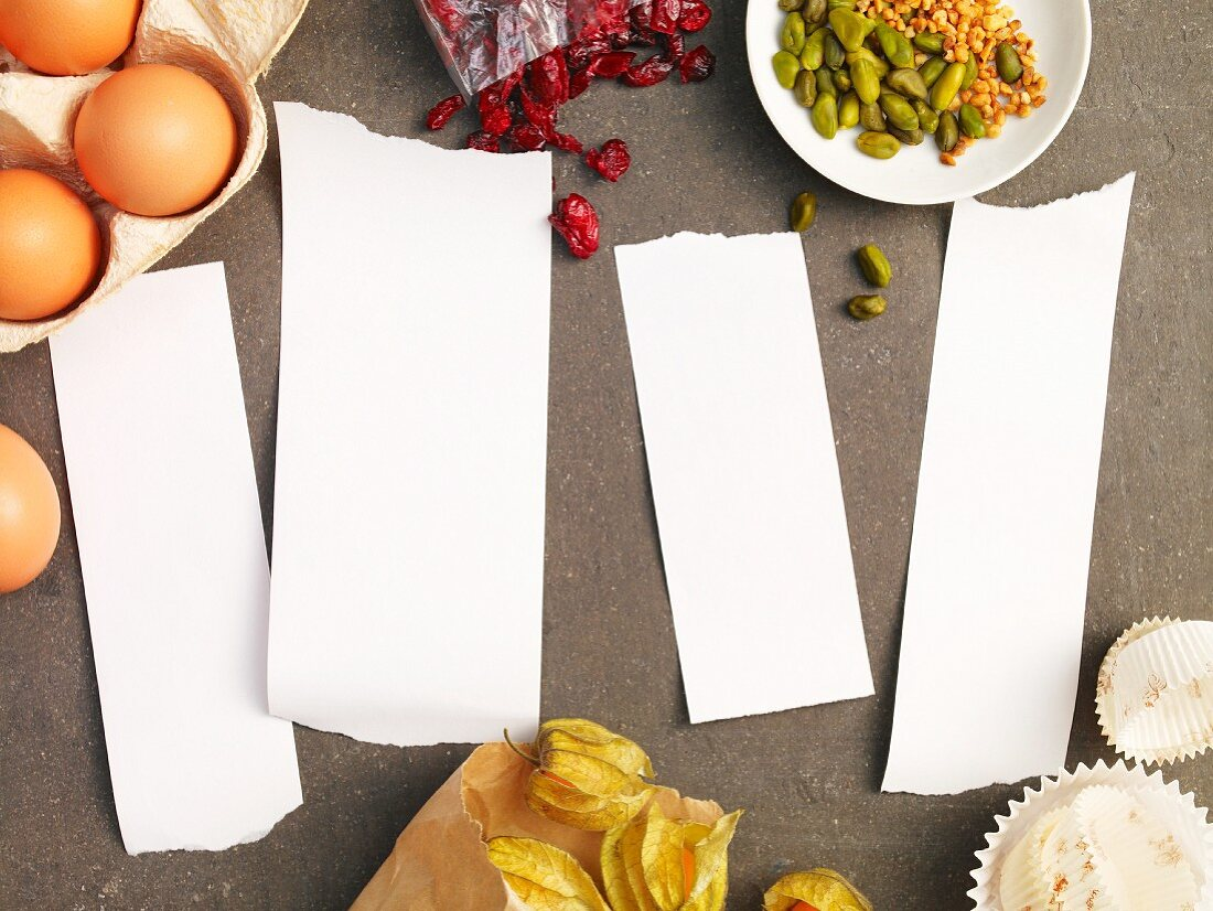 Four blank pieces of paper surrounded by ingredients for muffins