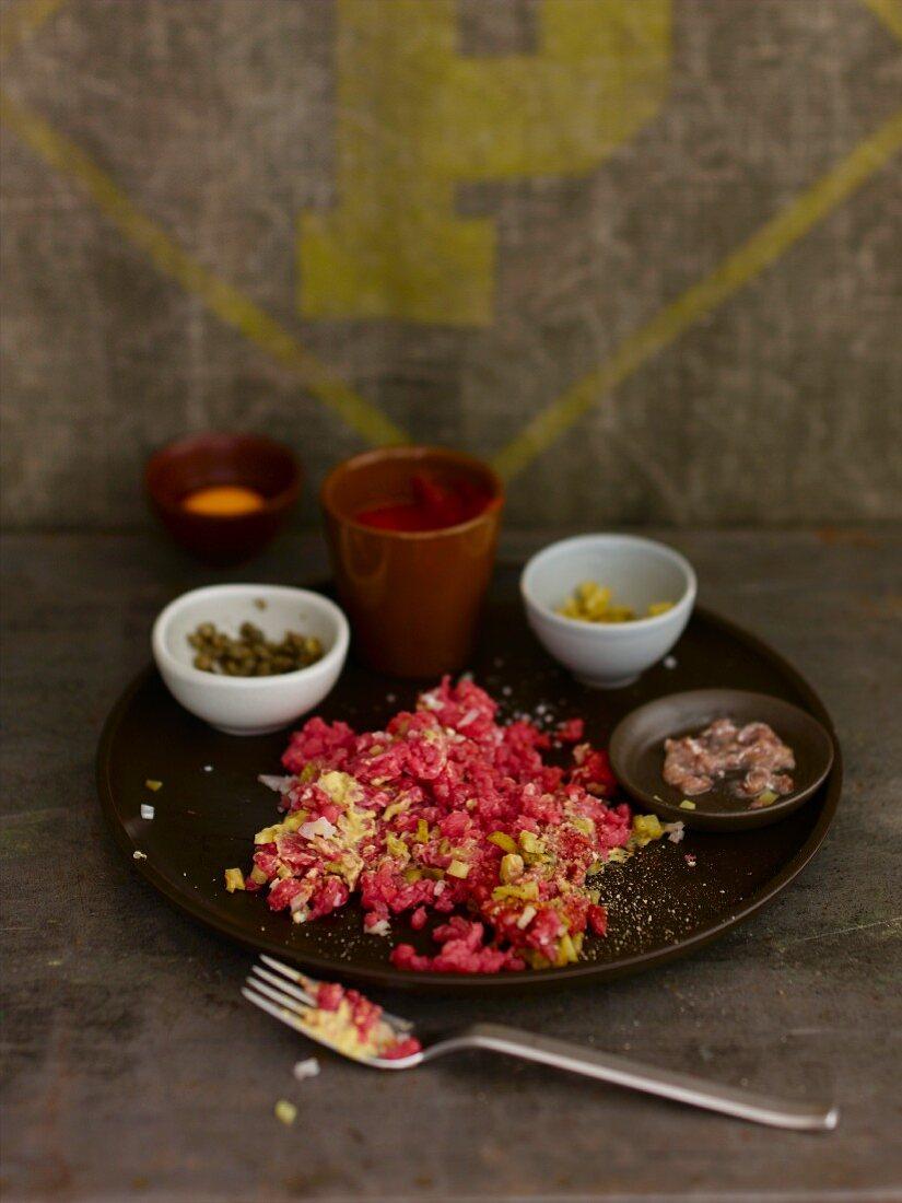 Beef tartar and ingredients in separate bowls
