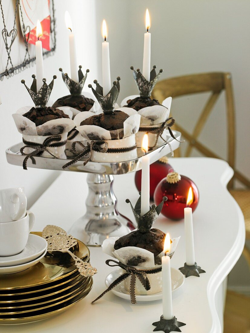 Chocolate muffins in paper cases on a silver cake stand with a stack of golden plates, candles and Christmas decorations next to it