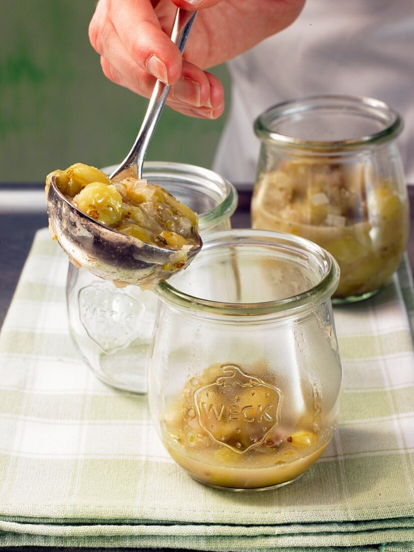 Gooseberry compote being transferred into jars