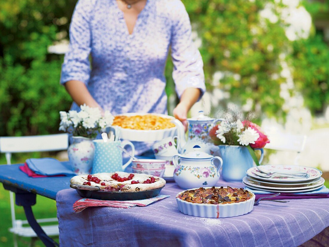 A woman laying a table in a garden with various cakes