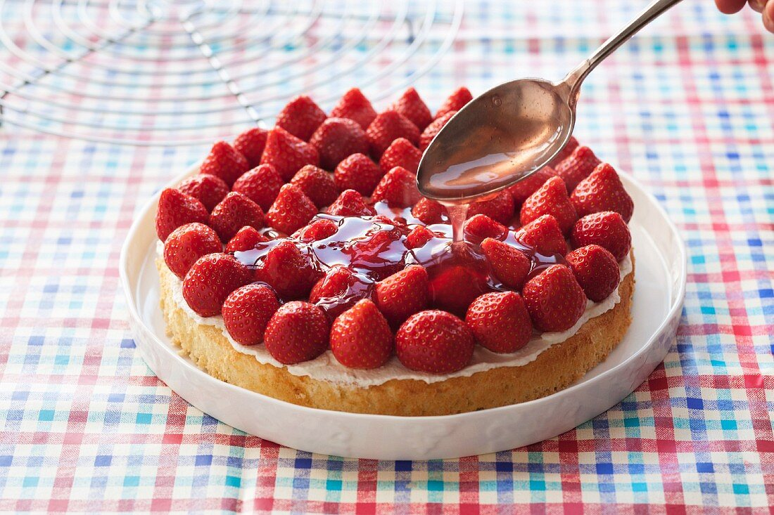 Strawberry cake being made: glaze being poured over the finished cake