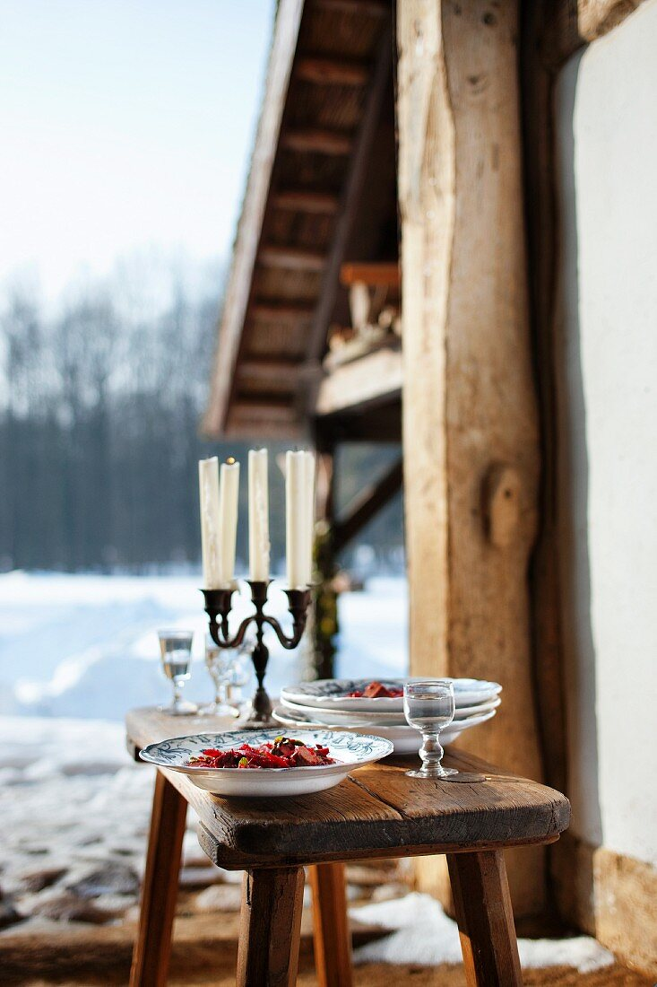 Stew and a candleholder on wooden table in front of a wintry hut