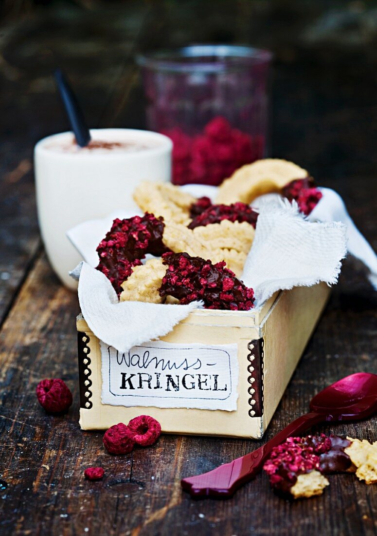Piped ring biscuits with walnuts, chocolate glaze and raspberries