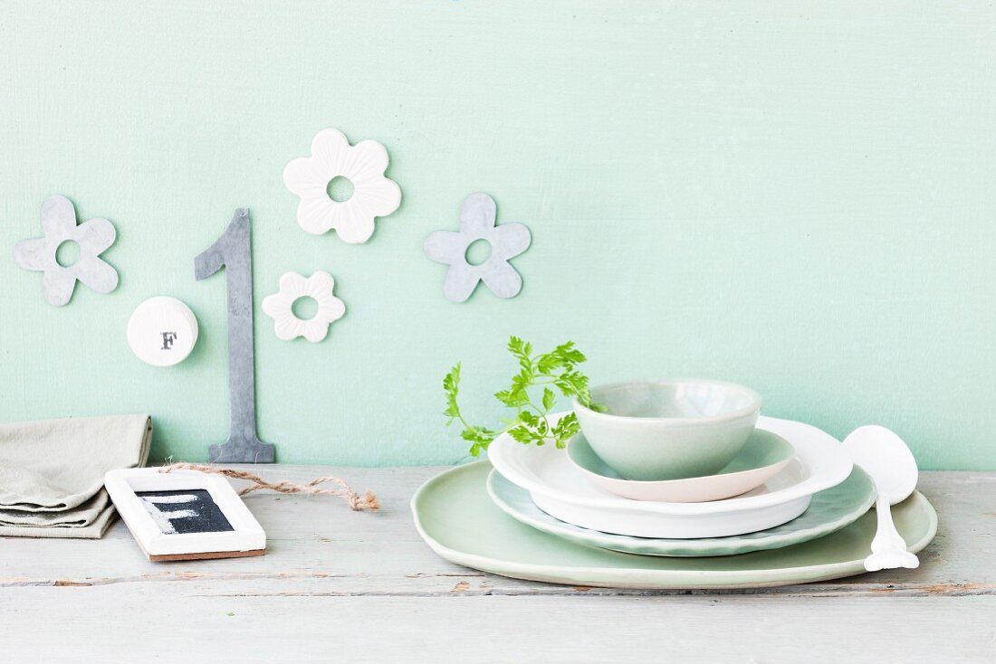 Pastel and white crockery against a wall decorated with flowers and a number 1