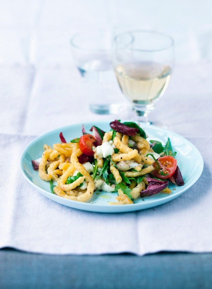Spätzle (soft egg noodles from Swabia) with rocket, chicory and cherry tomatoes