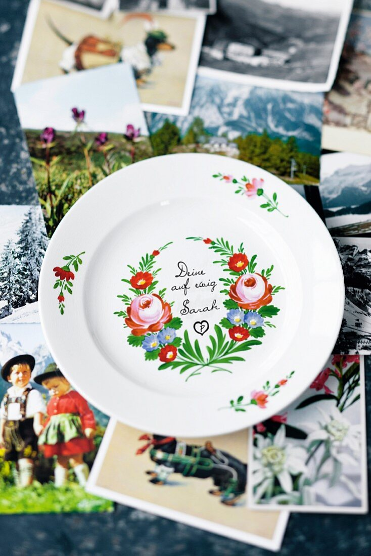 A hand-painted plate on top of a selection of alpine photos