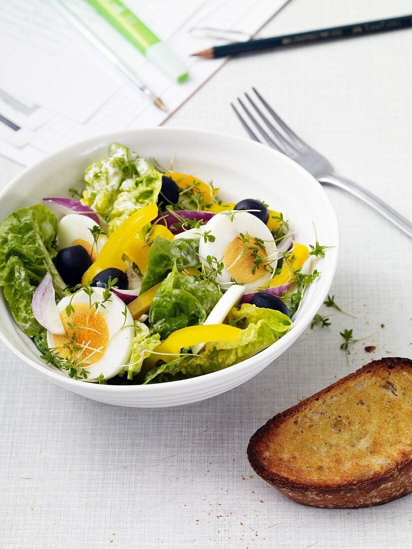 Mixed leaf salad with eggs, peppers, olives and garlic bread