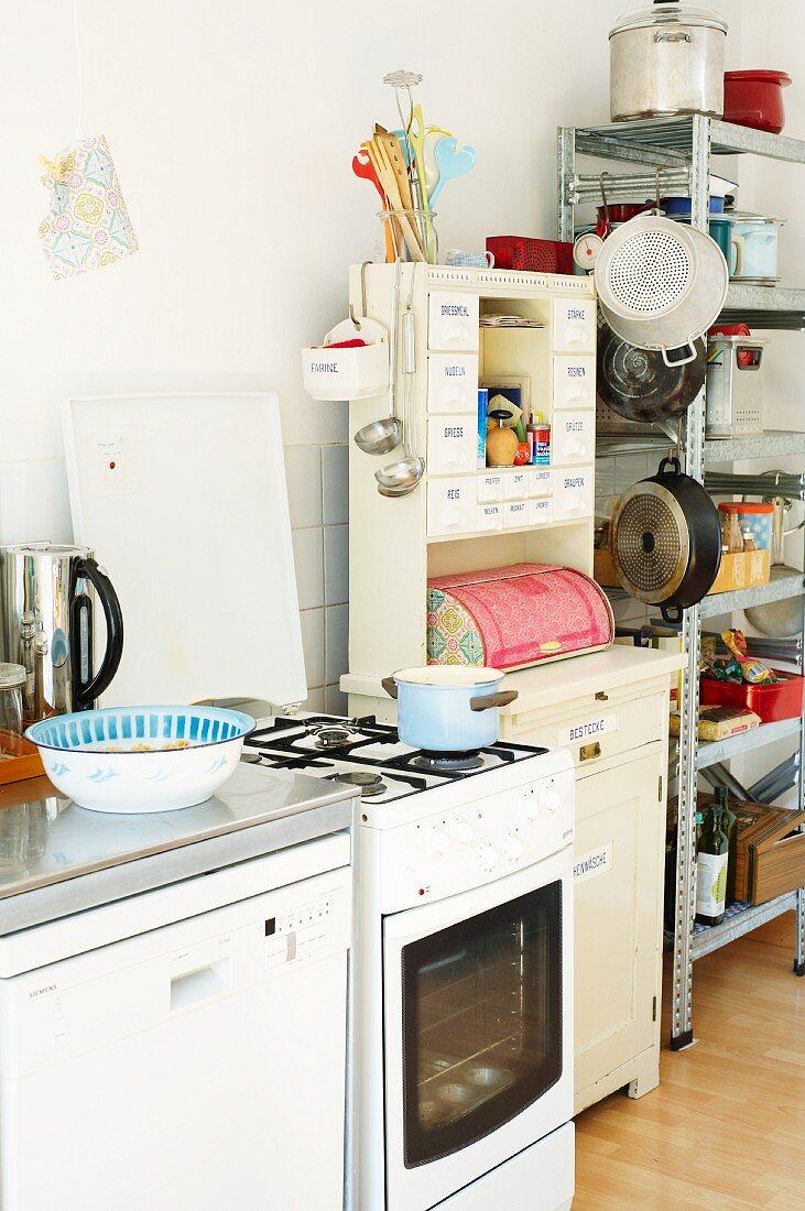 Cooker & utensils on shelves in students' kitchen