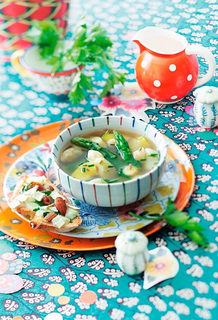 Kartoffel-Spargel-Suppe und Kräuterbrot auf bunt dekoriertem Tisch