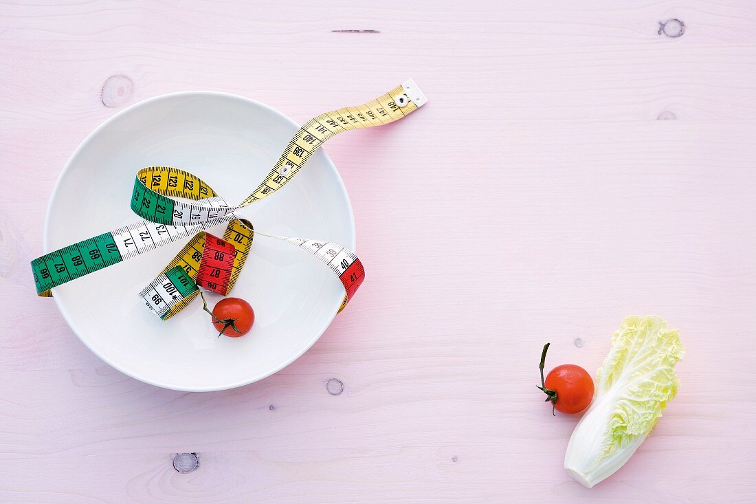 A symbolic image for a diet: a measuring tape on a plate
