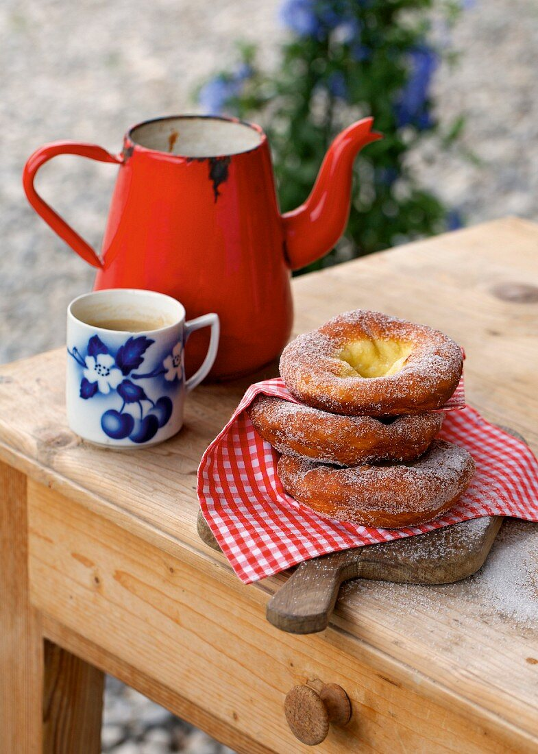 Ausgezogene (Bavarian-style doughnuts) next to a coffee cup and an enamel jug on a wooden table (Germany)