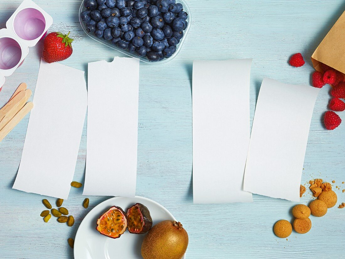 Four pieces of paper surrounded by ingredients for desserts