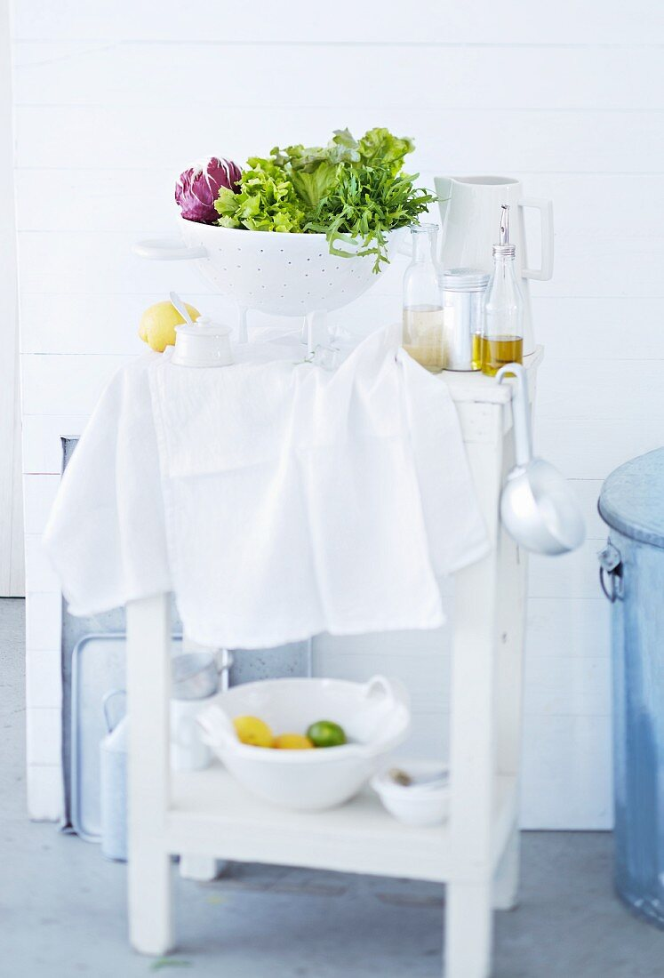 Salad in a colander and dressing ingredients on a kitchen side table