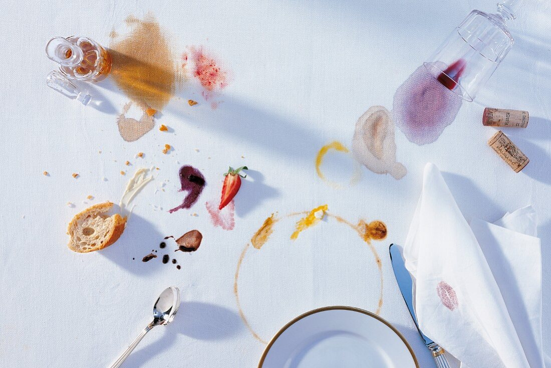 Overhead view of various stains and leftovers on white tablecloth