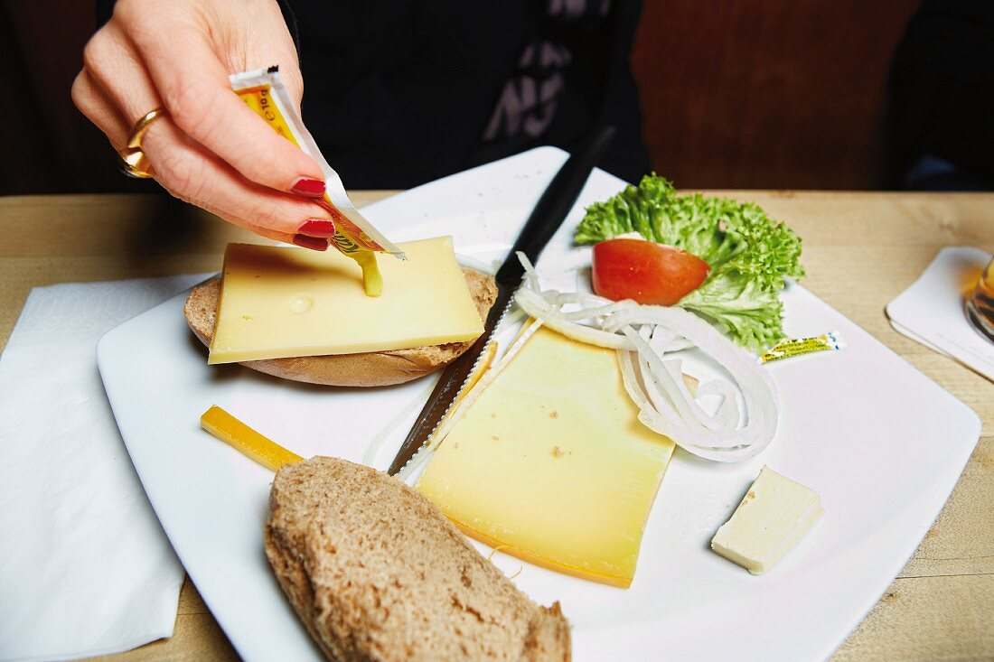 A cheese sandwich being spread with mustard