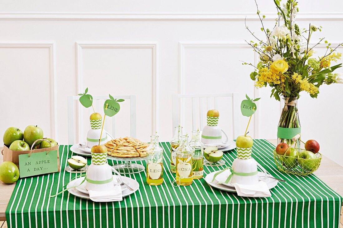 A table laid with a green-and-white striped tablecloth and fresh apples