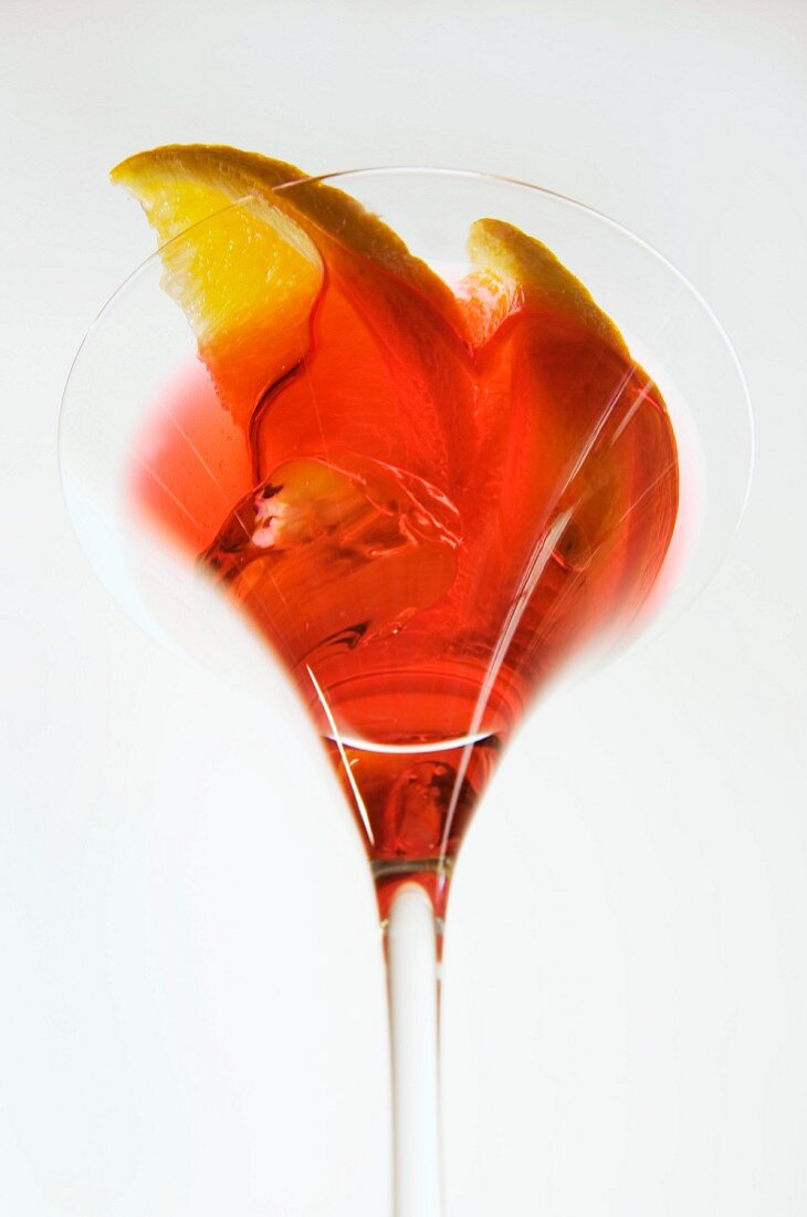 A red cocktail with wedges of orange