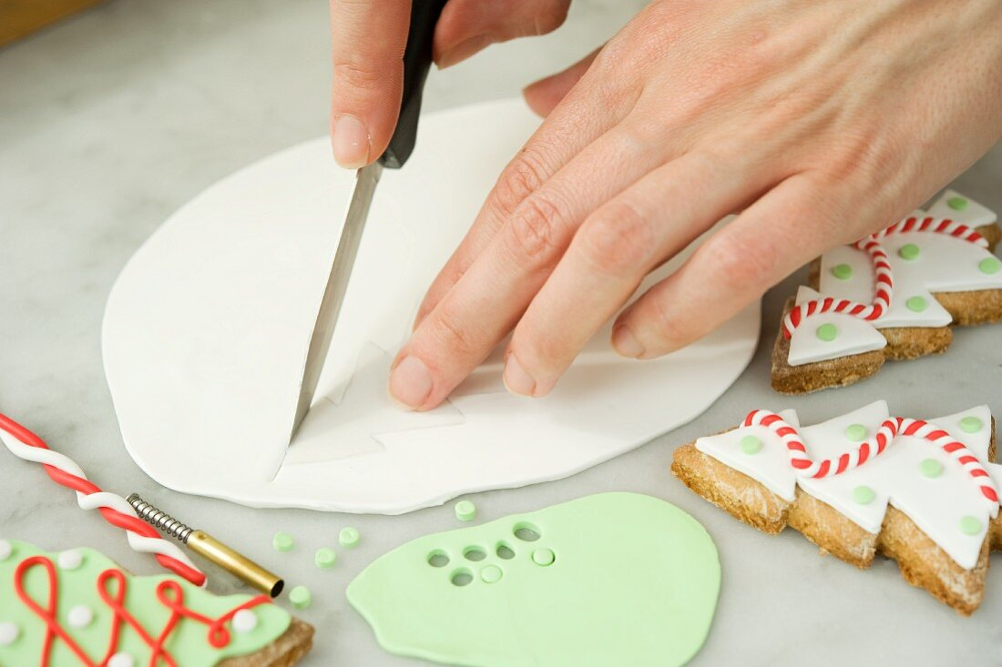 Biscuit decorations being cut out of fondant with decorated Christmas tree biscuits next to it