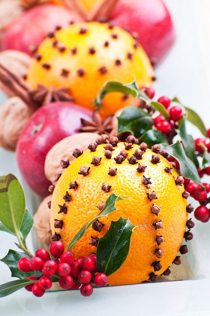 Oranges pierced with cloves, holly berries, apples, walnuts, star anies and cinnamon sticks