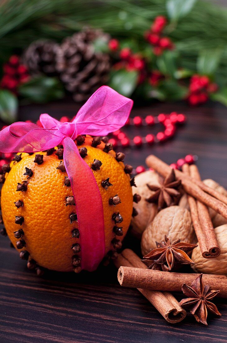 An orange pierced with clove tied with a pink ribbon with walnuts and spices