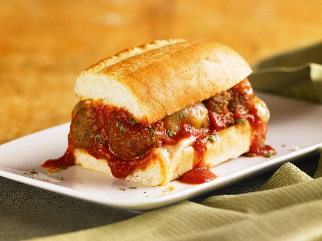 Meatball Sub with Marinara Sauce Dripping Down the Sides; On a White Plate