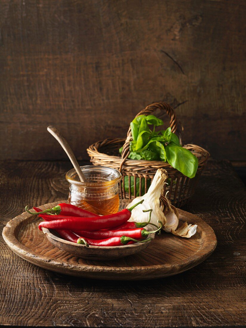 Chilis, honey, garlic and basil on board