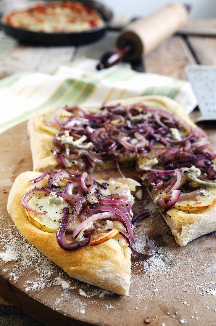 Pizza topped with gorgonzola cheese, red onions and apple slices