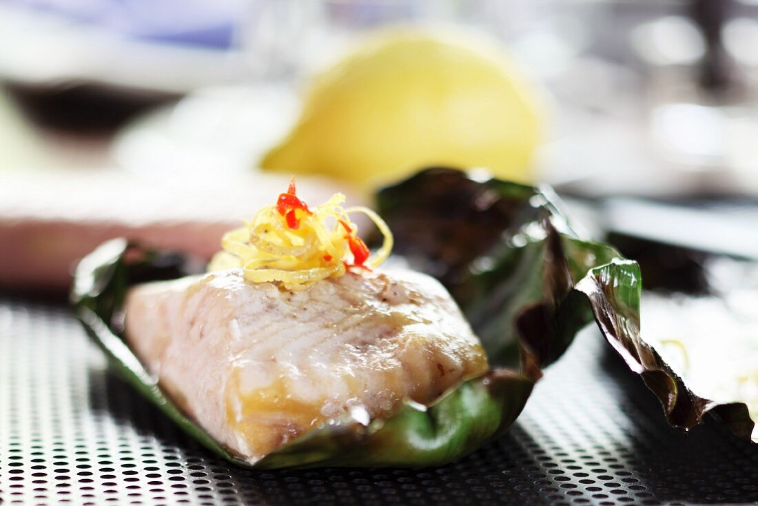 Grilled sturgeon with lemon zest wrapped in a banana leaf