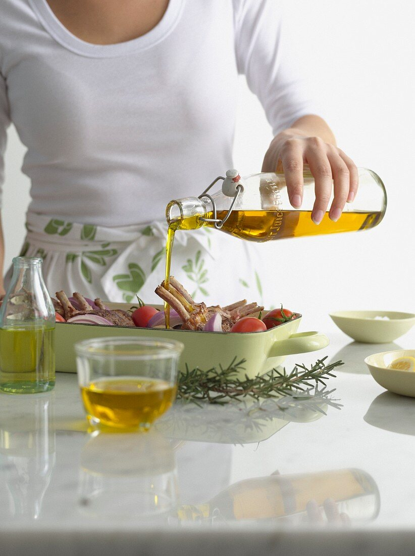 Woman pouring olive oil over roast dish