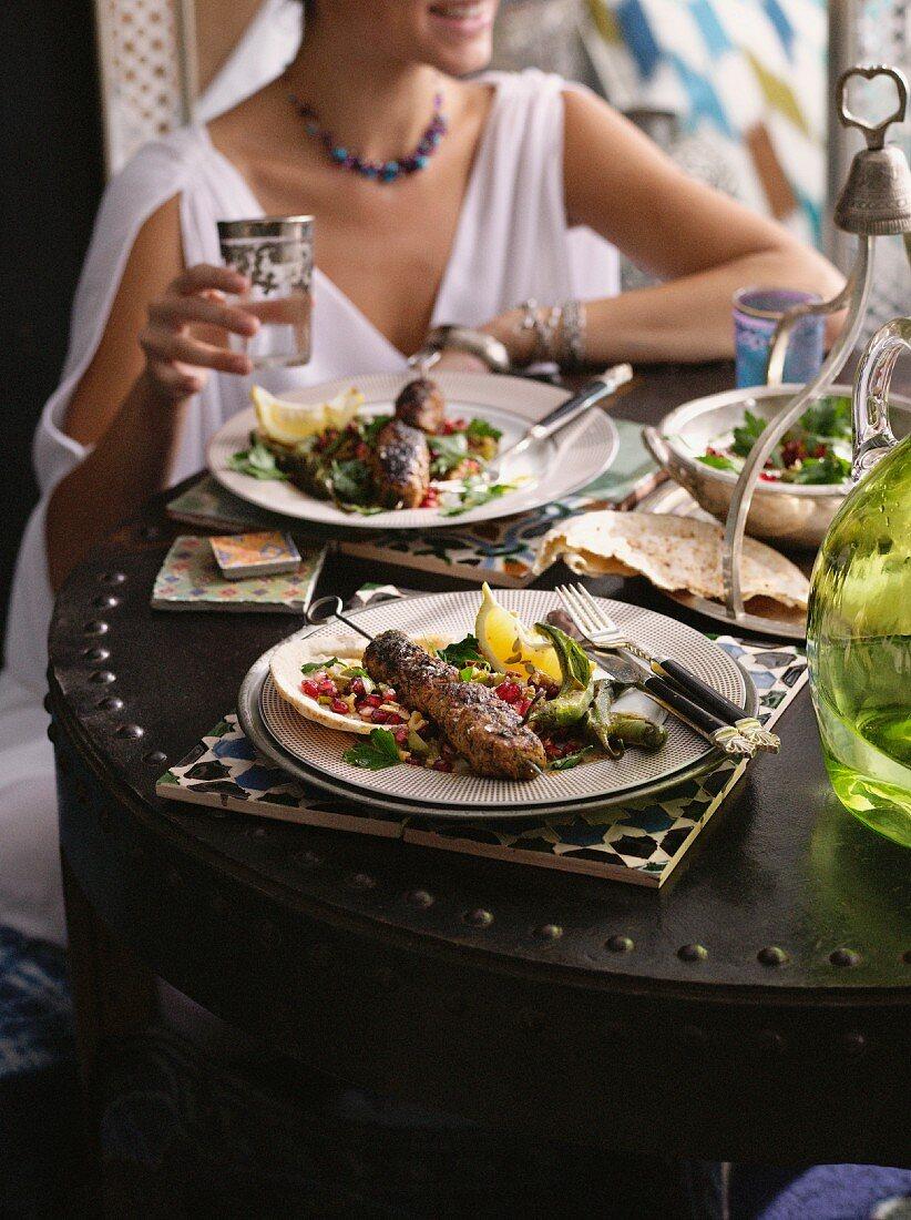 Frau sitzt beim Abendessen in einem türkischen Restaurant