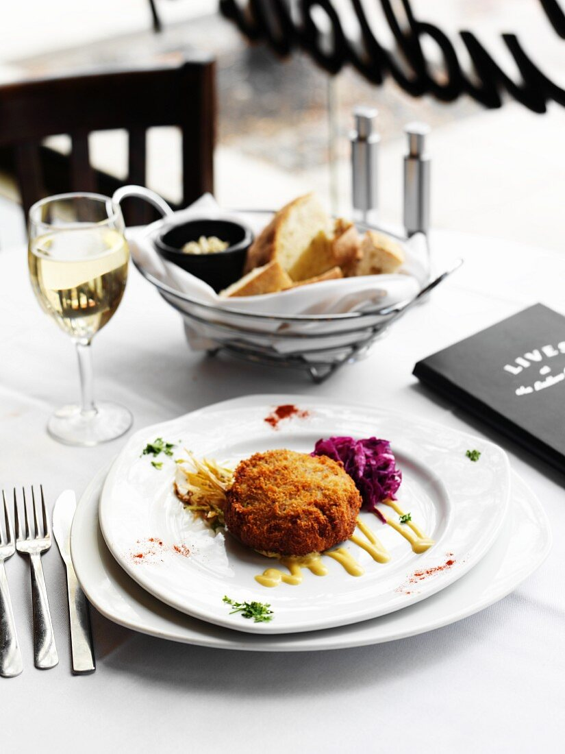 Crab Cake Appetizer at a Restaurant Table with a Glass of White Wine and Basket of Bread