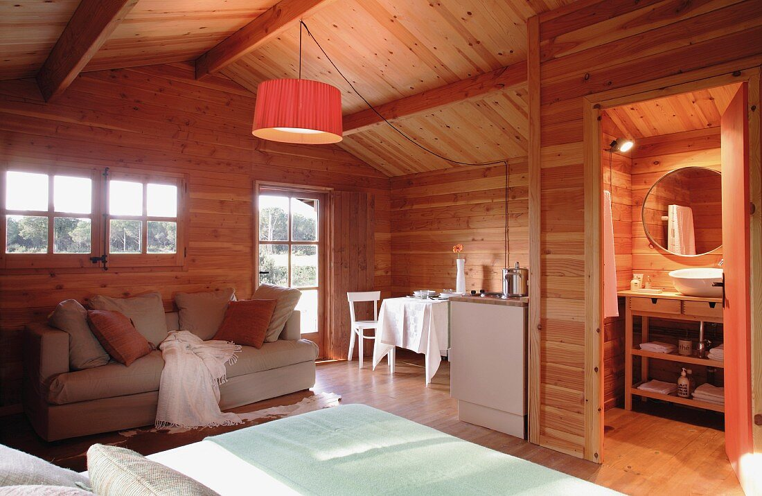 Open-plan living space in a cosy wooden house; a central pendant lamp provides a warm light
