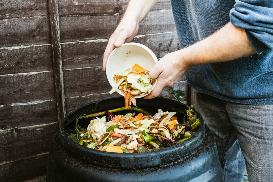 Man adding to compost bin outdoors