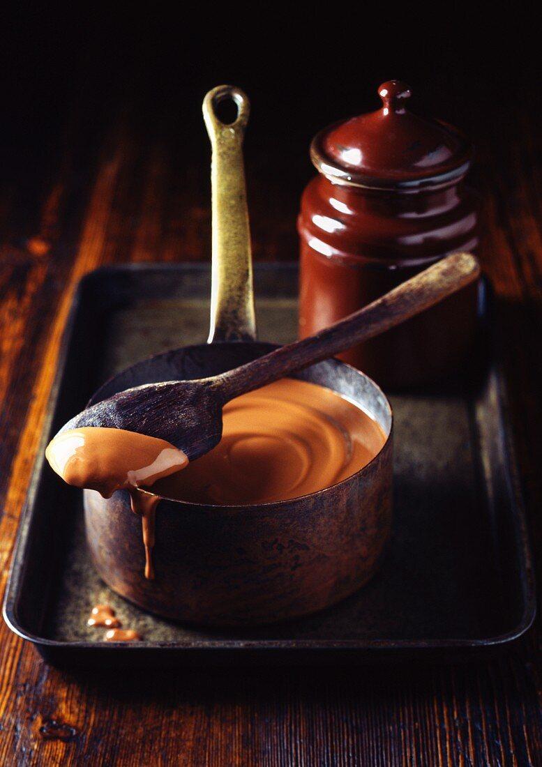 Pot of caramel sauce on tray