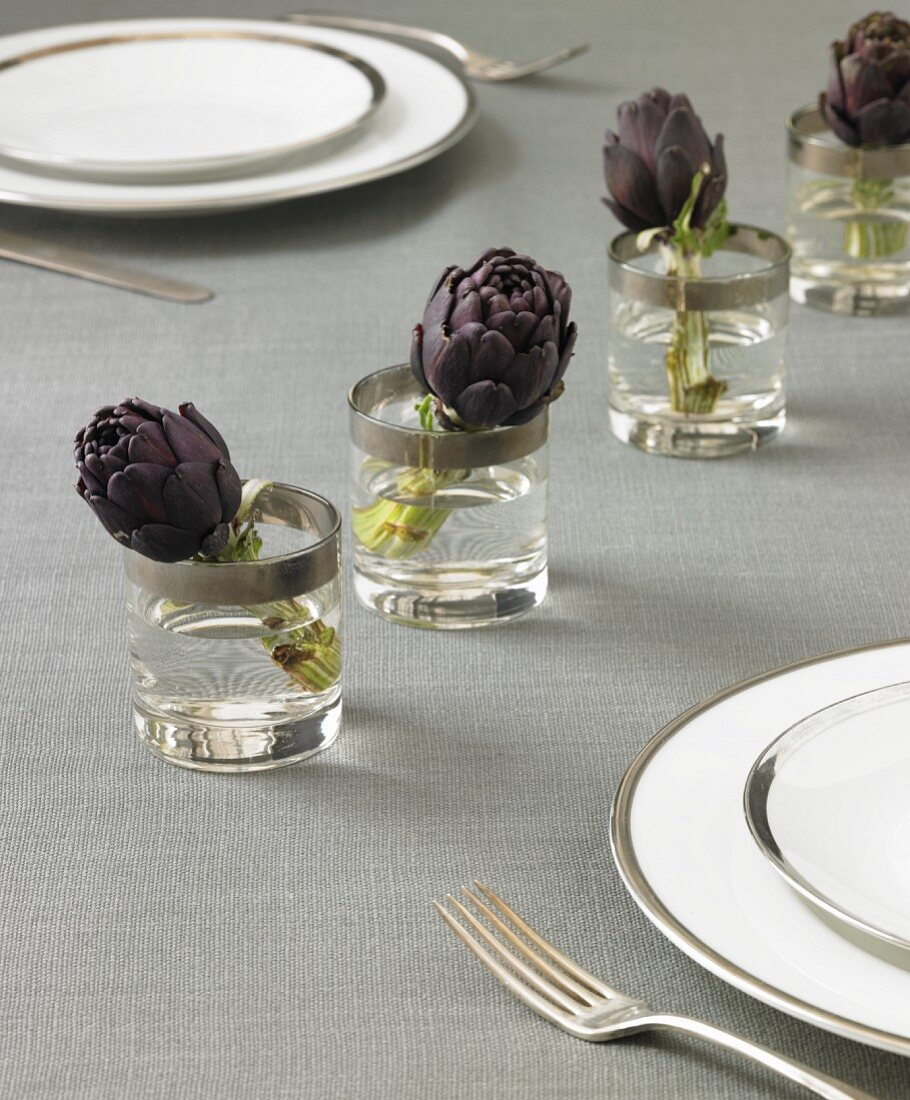Table Setting with Artichokes in Glasses of Water