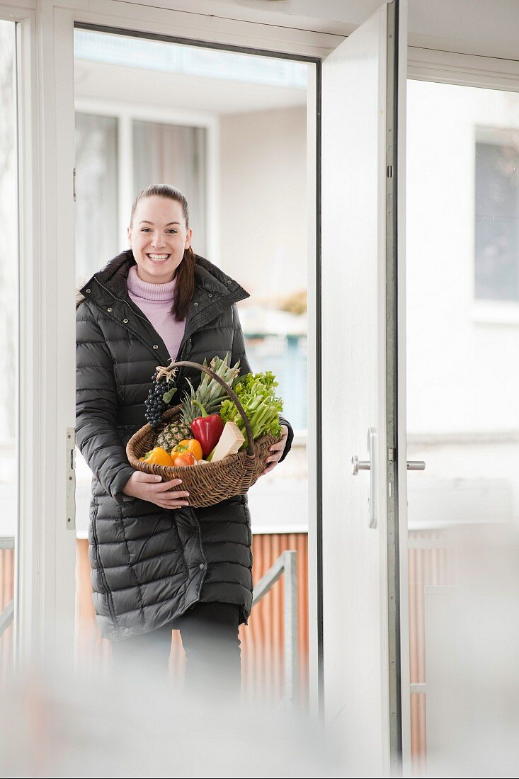 Smiling woman with basket of produce