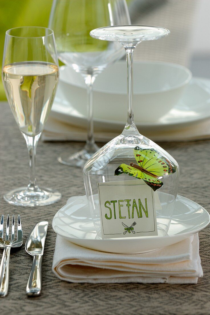 A butterfly decoration and a name label caught under a wine glass on a table