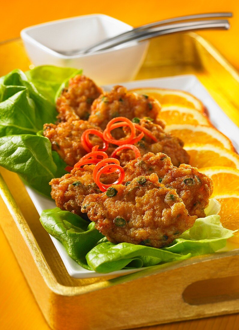 Shrimp cakes on a platter with lettuce and orange slices