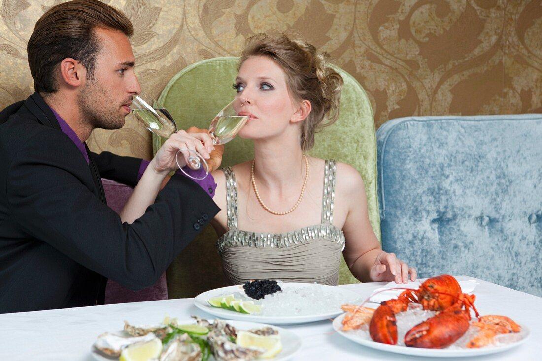 Paar in Abendkleidung trinkt Sekt zu Hummer und Austern